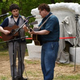 jacob and david bernz playing guitar in front of puffin's pete seeger statue