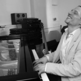 fernando otero smiling playing his piano in black and white