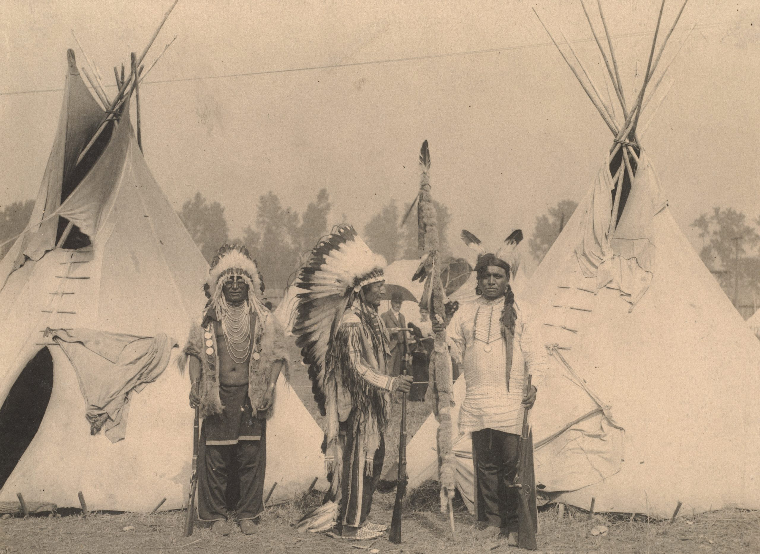 Black Foot, Standing Bear, Big Eagle, Sioux. Three members of the Sioux tribe pose in Indian Village, 1898